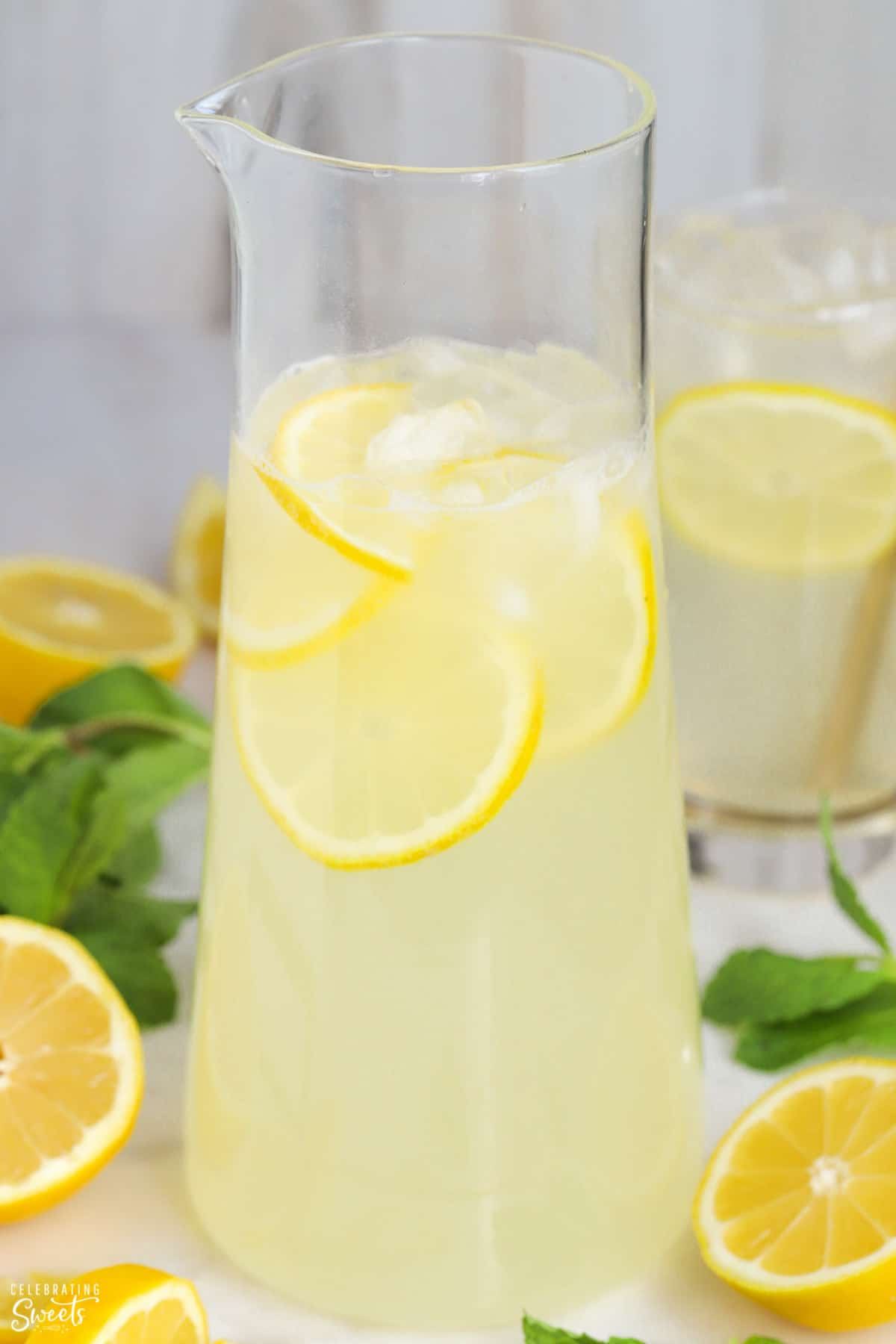 Pitcher of lemonade garnished with fresh lemon.