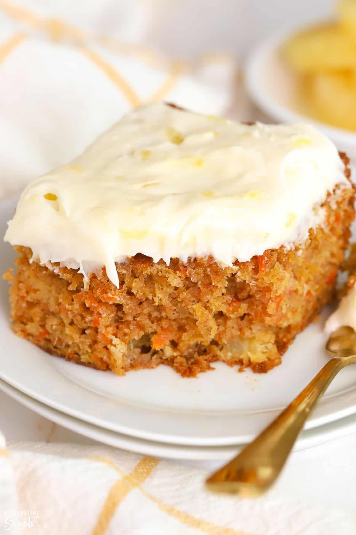 Slice of Pineapple Carrot Cake on a white plate with a gold fork