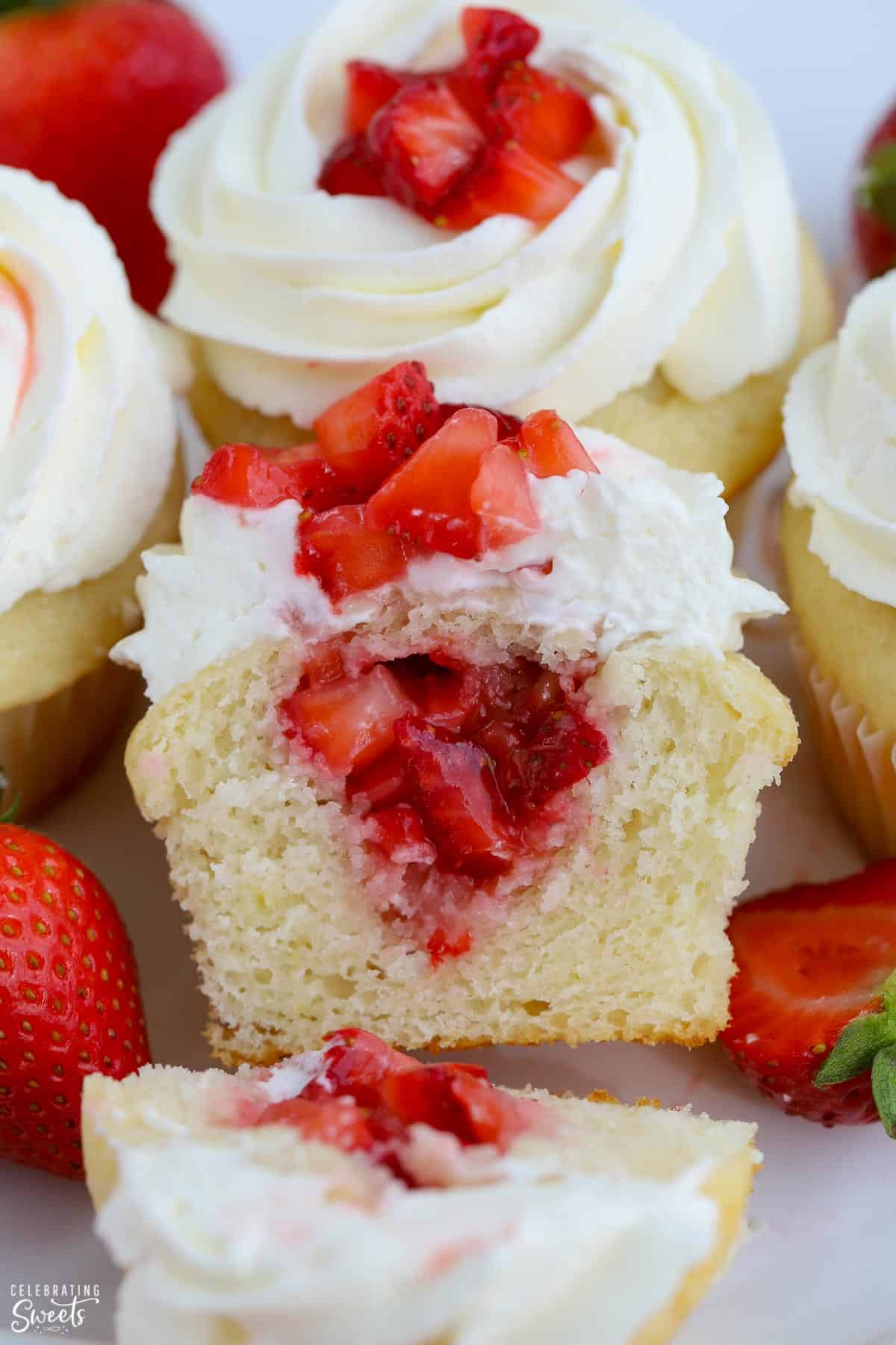 Vanilla cupcake cut in half with diced strawberries inside the cupcake.