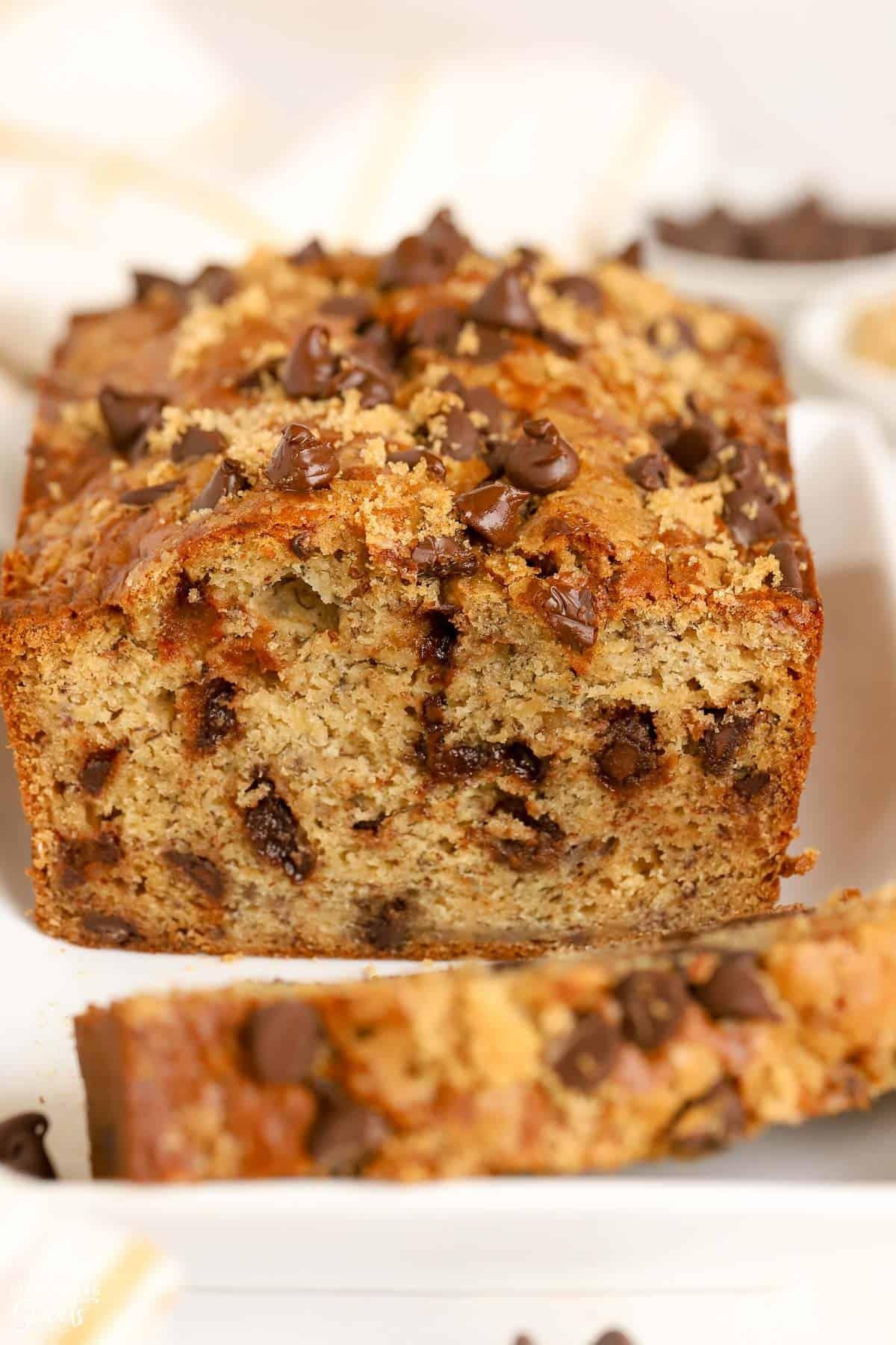 Closeup of a loaf of chocolate chip banana bread on a white plate.