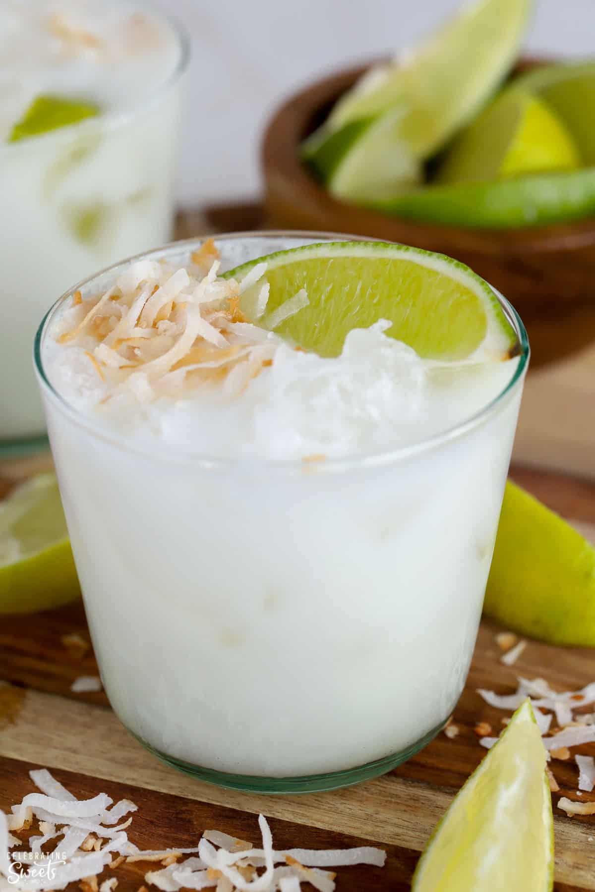 Closeup of a coconut margarita in a glass garnished with toasted coconut and lime