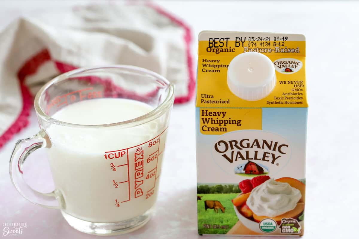 Heavy cream in a carton and milk in a glass measuring cup