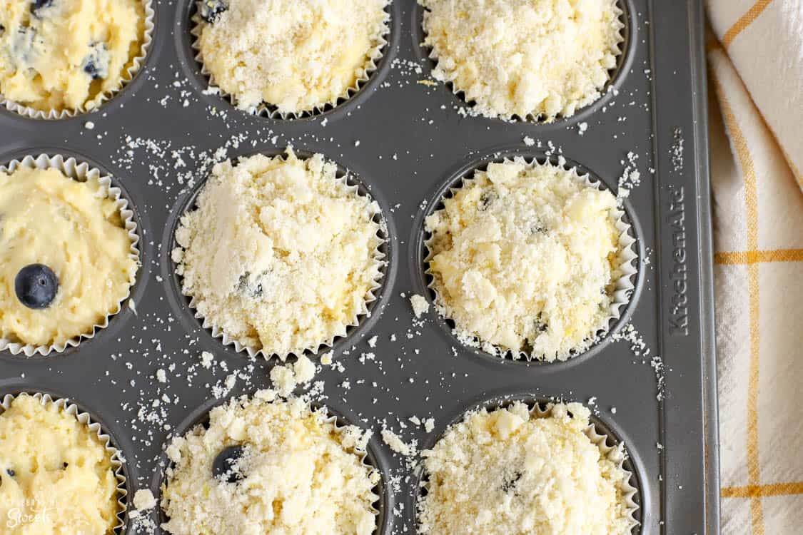 Muffin batter in a muffin tin topped with crumb topping.