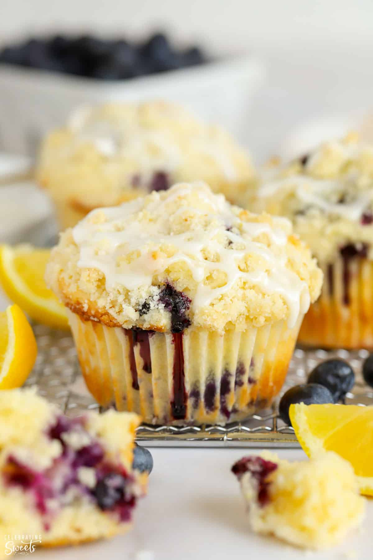 Closeup of a lemon blueberry muffin with crumb topping and white icing