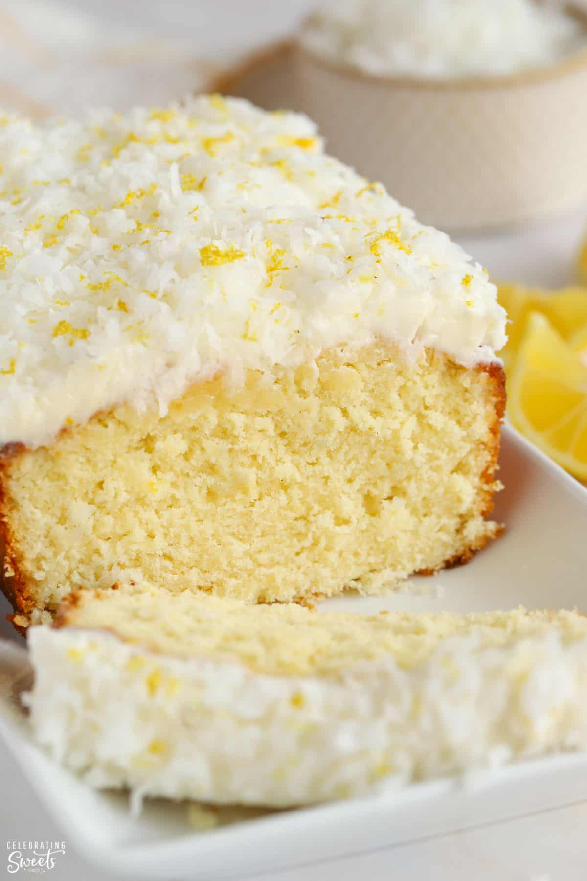 Lemon Coconut loaf cake topped with frosting and shredded coconut