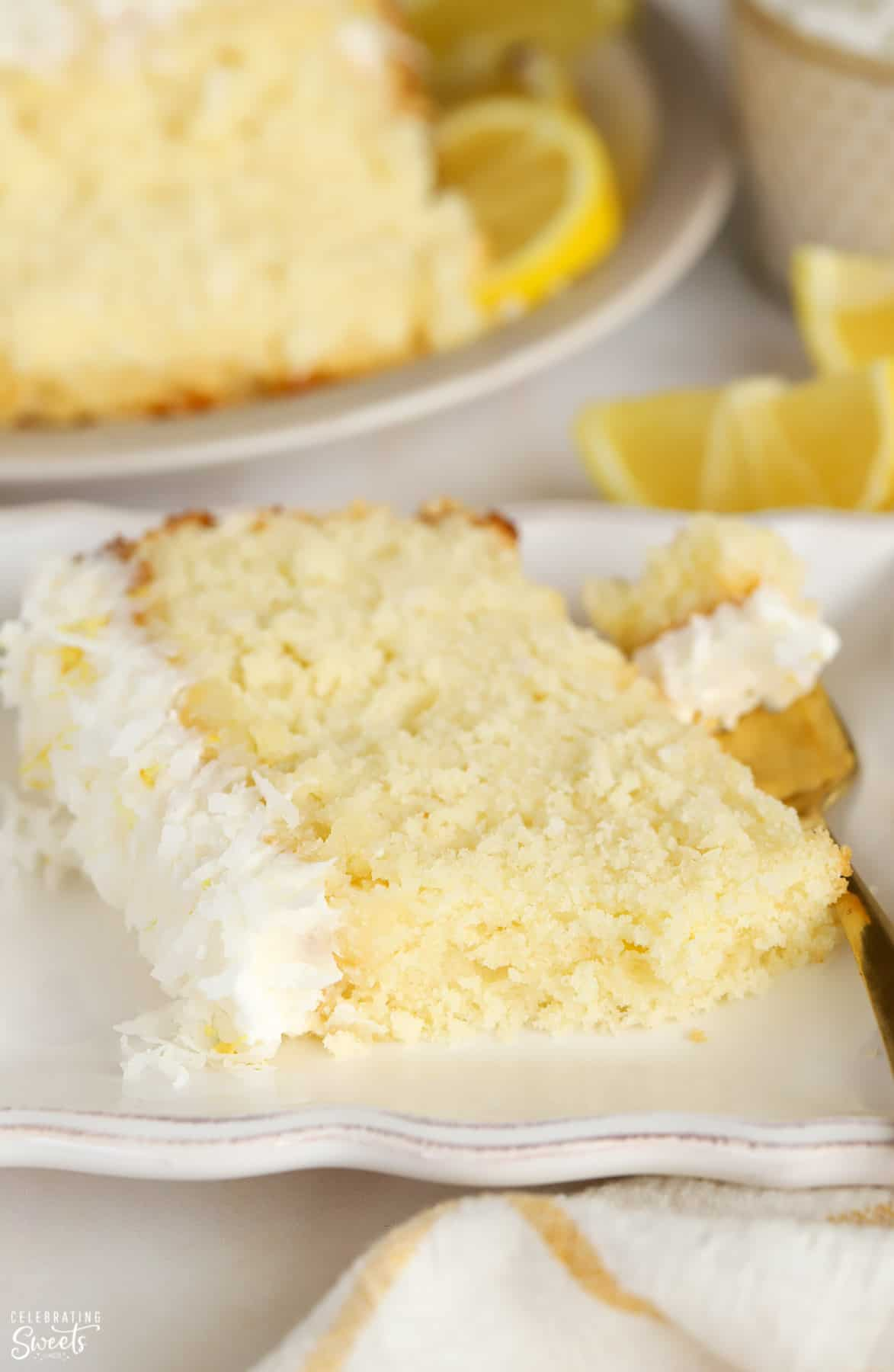 Slice of lemon coconut cake on a white plate with a gold fork