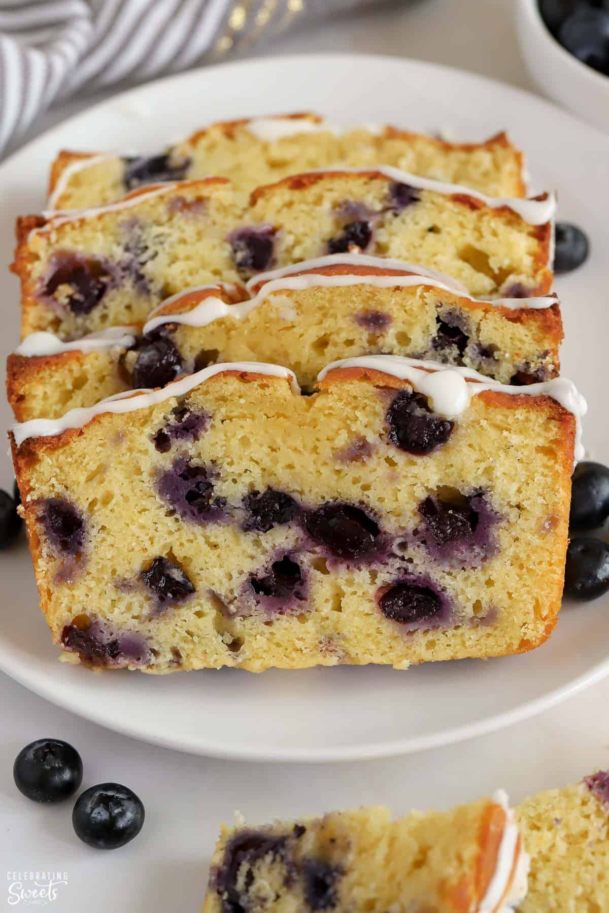 Four slices of blueberry bread on a white plate.