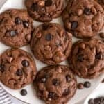 Chocolate cookies topped with chocolate chips on a white plate
