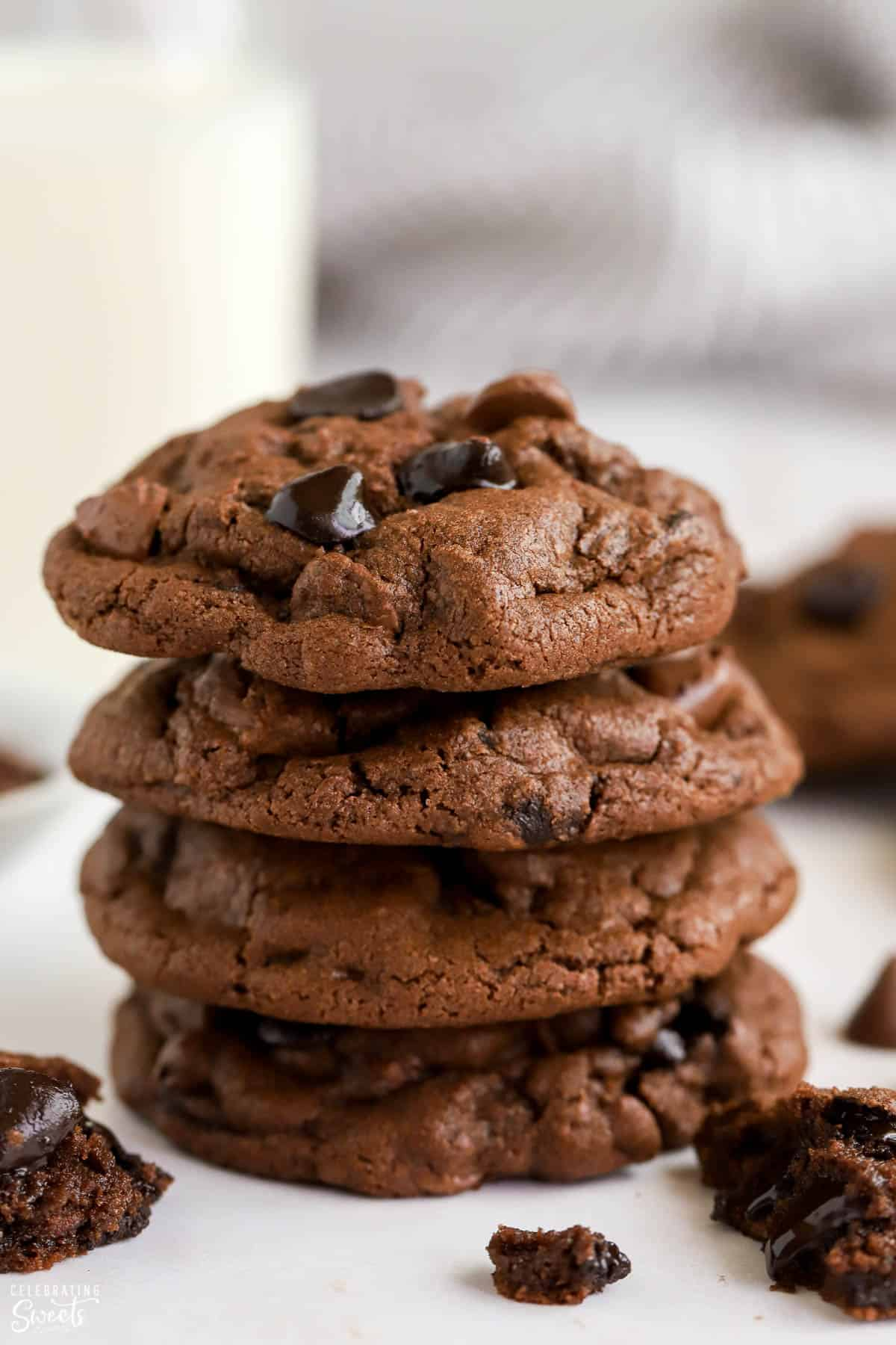 Stack of four chocolate cookies with milk in the background