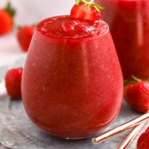 Dark red Frosé wine slushies in a glass garnished with strawberries.