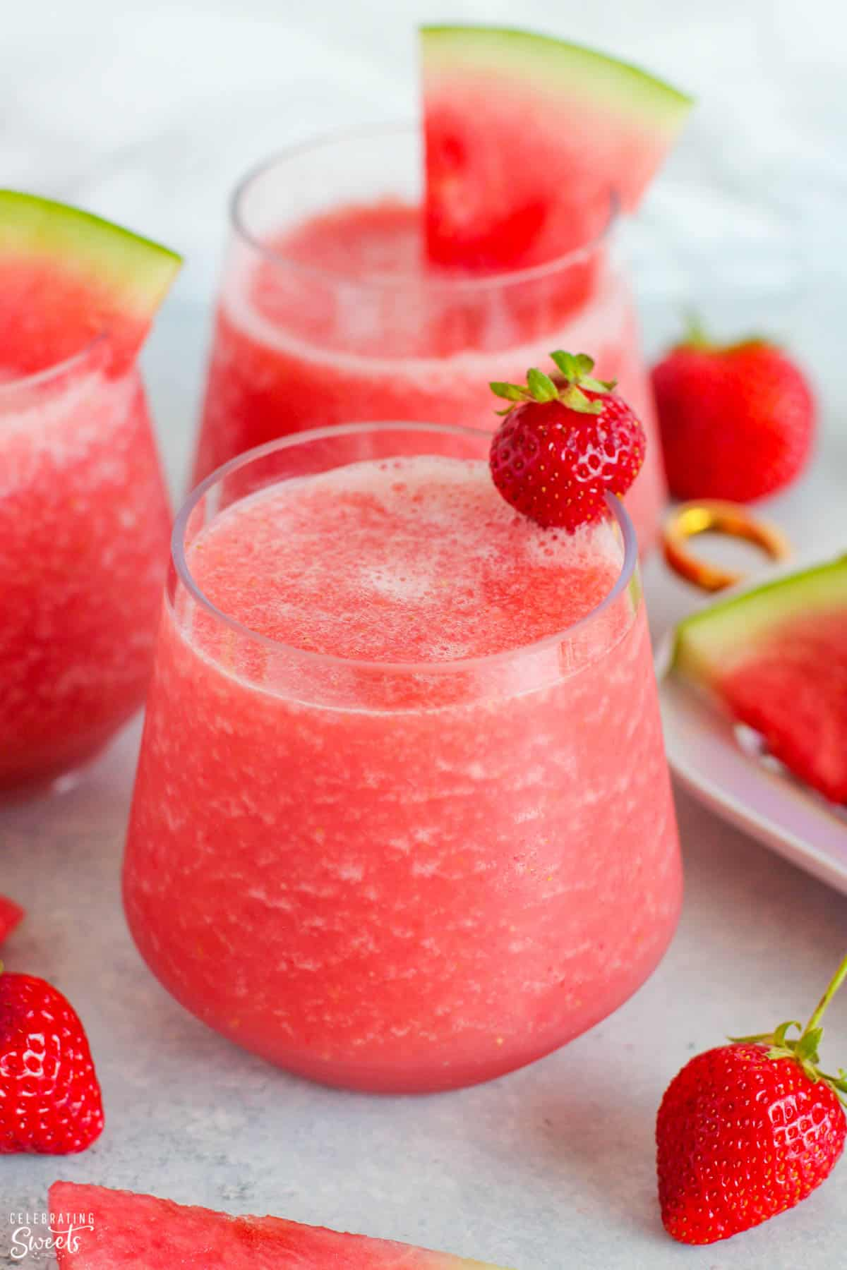Pink Frosé wine slushies in a glass garnished with strawberries and watermelon.
