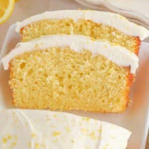 Two slices of lemon loaf cake topped with frosting and lemon zest.