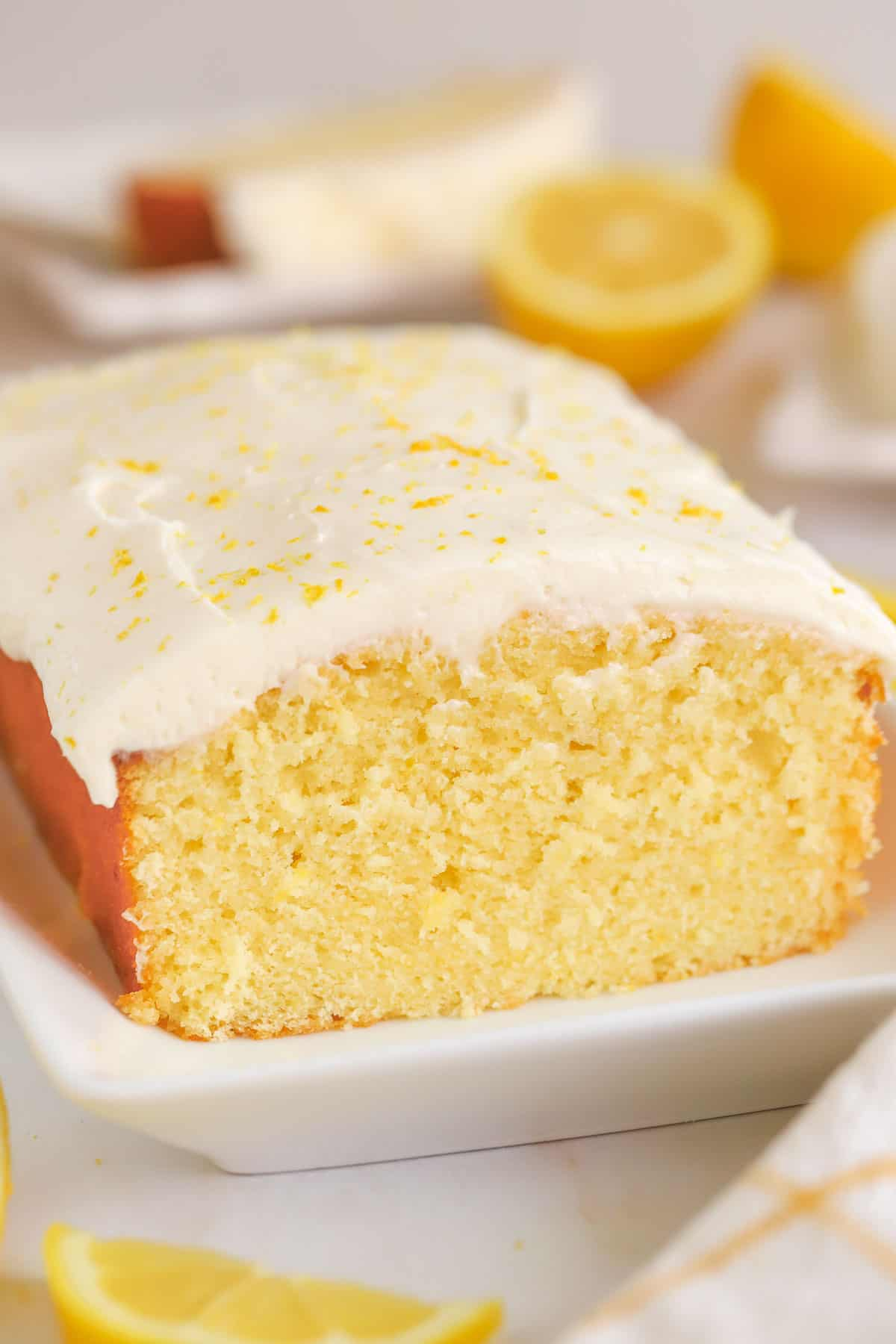 Lemon loaf cake topped with frosting on a white plate.