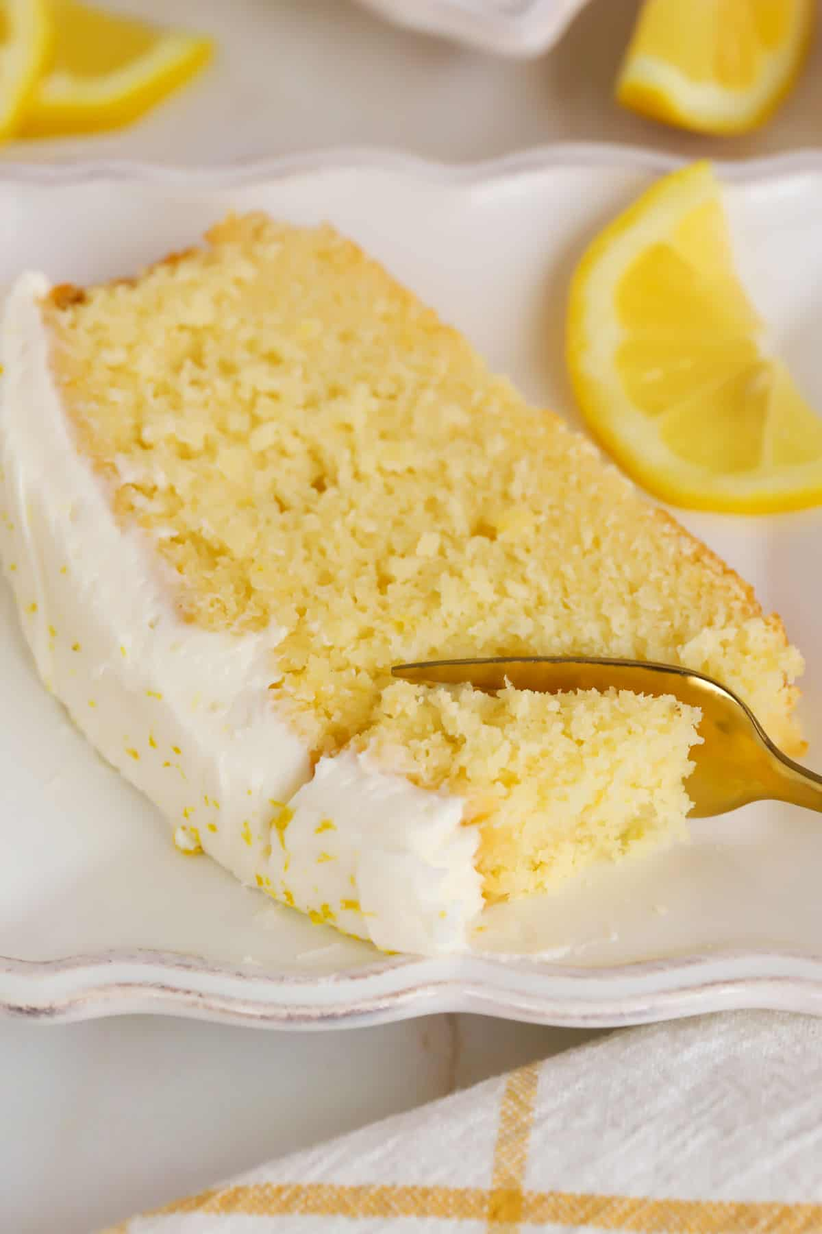 Slice of lemon loaf cake on a white plate with a gold fork.