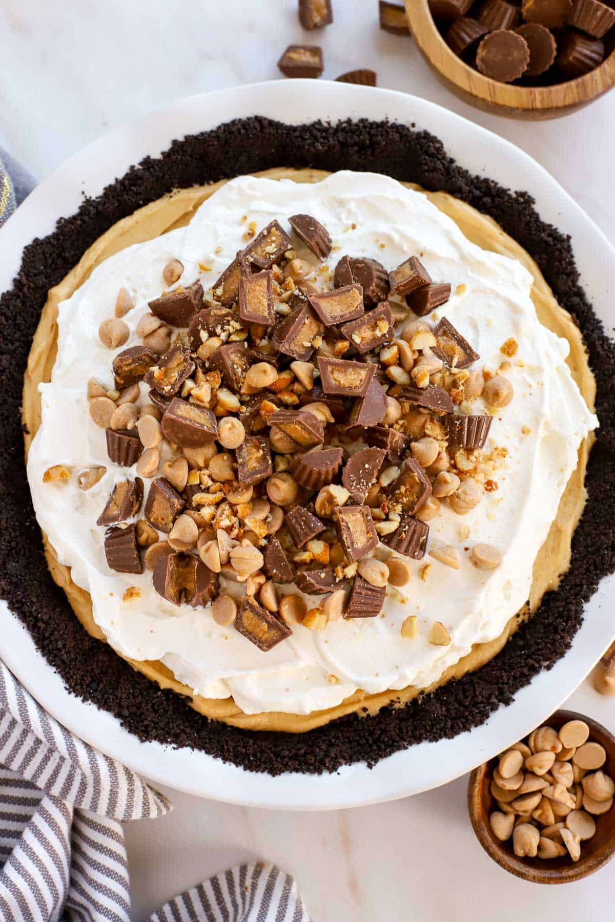 Overhead shot of peanut butter pie in a white pie plate topped with peanut butter cups and peanut butter chips.