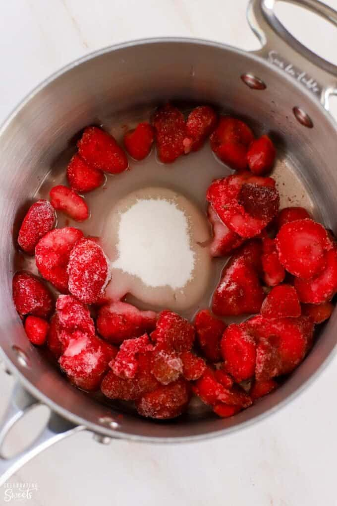 Frozen strawberries, sugar, and water in a saucepan.