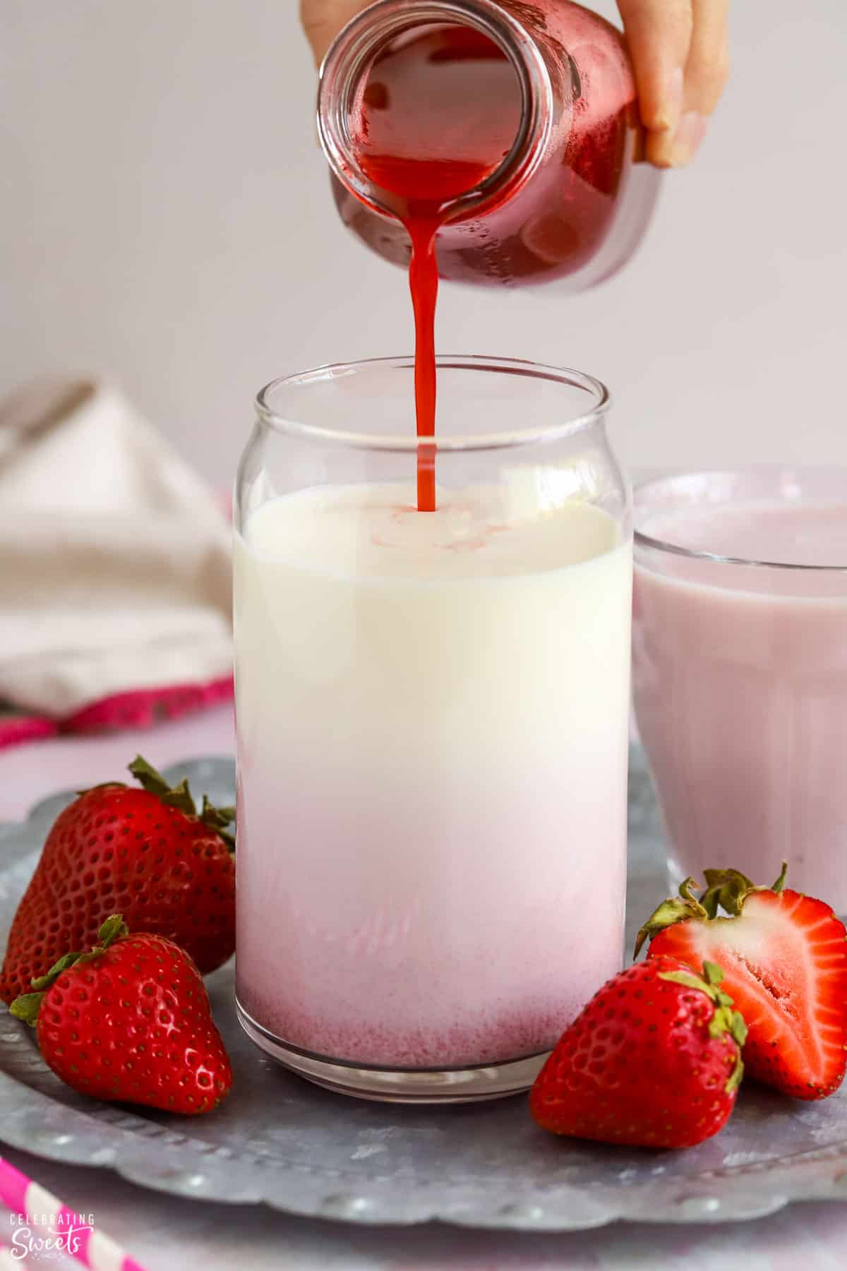 Strawberry syrup being poured into a glass of milk.