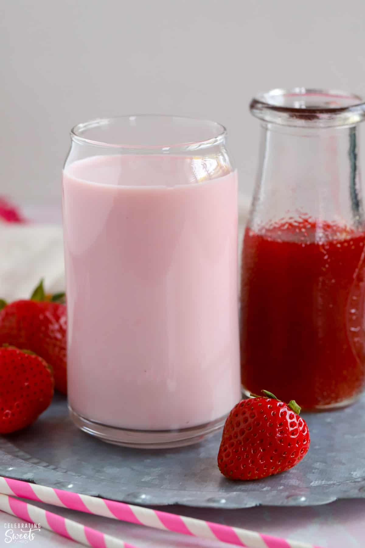 Glass of strawberry milk and a carafe of strawberry syrup.