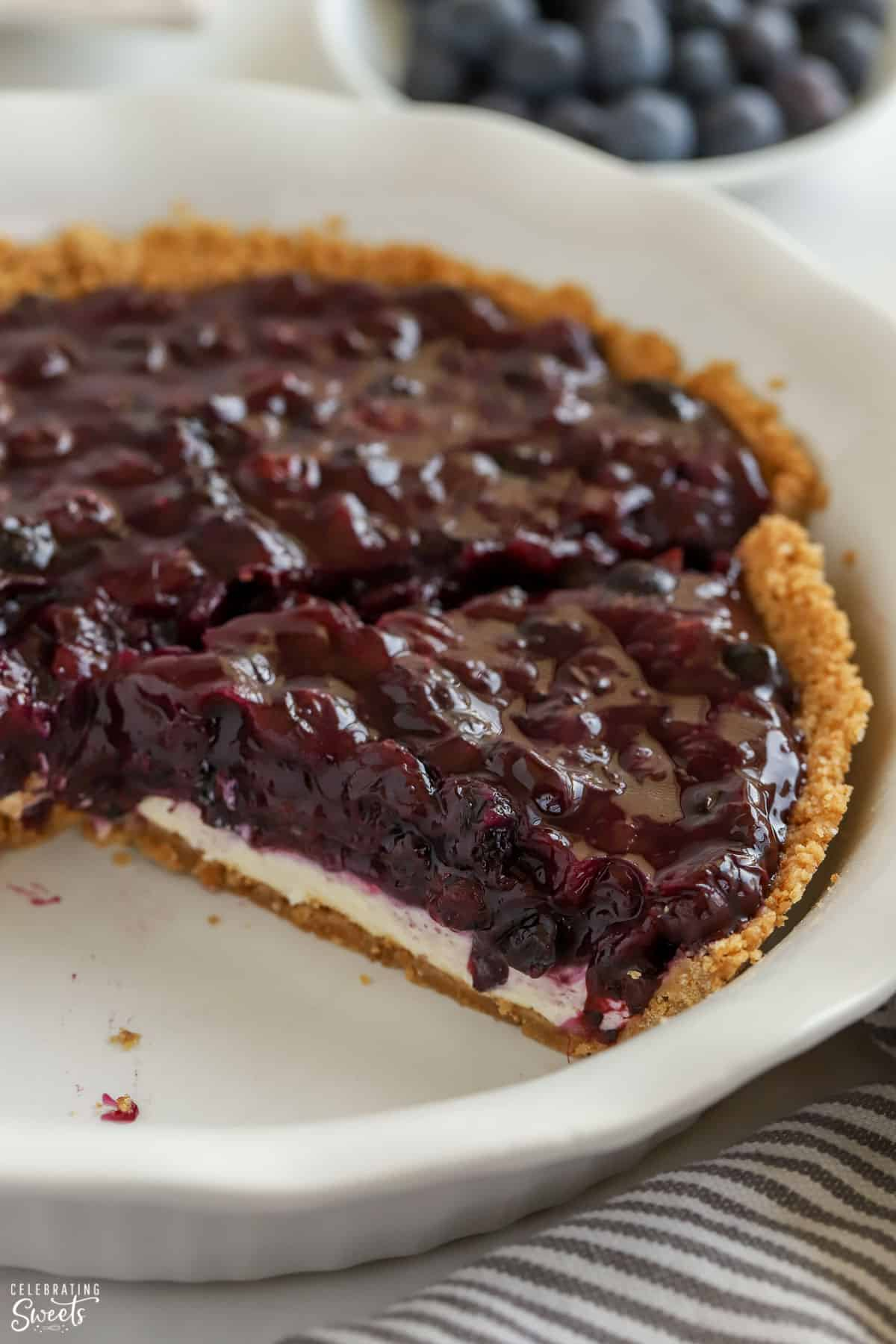 Blueberry Pie in a graham cracker crust with a white pie plate.