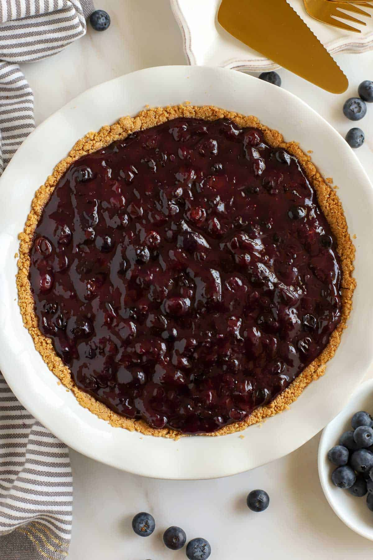 Blueberry pie filling in a graham cracker crust surrounded by fresh blueberries.