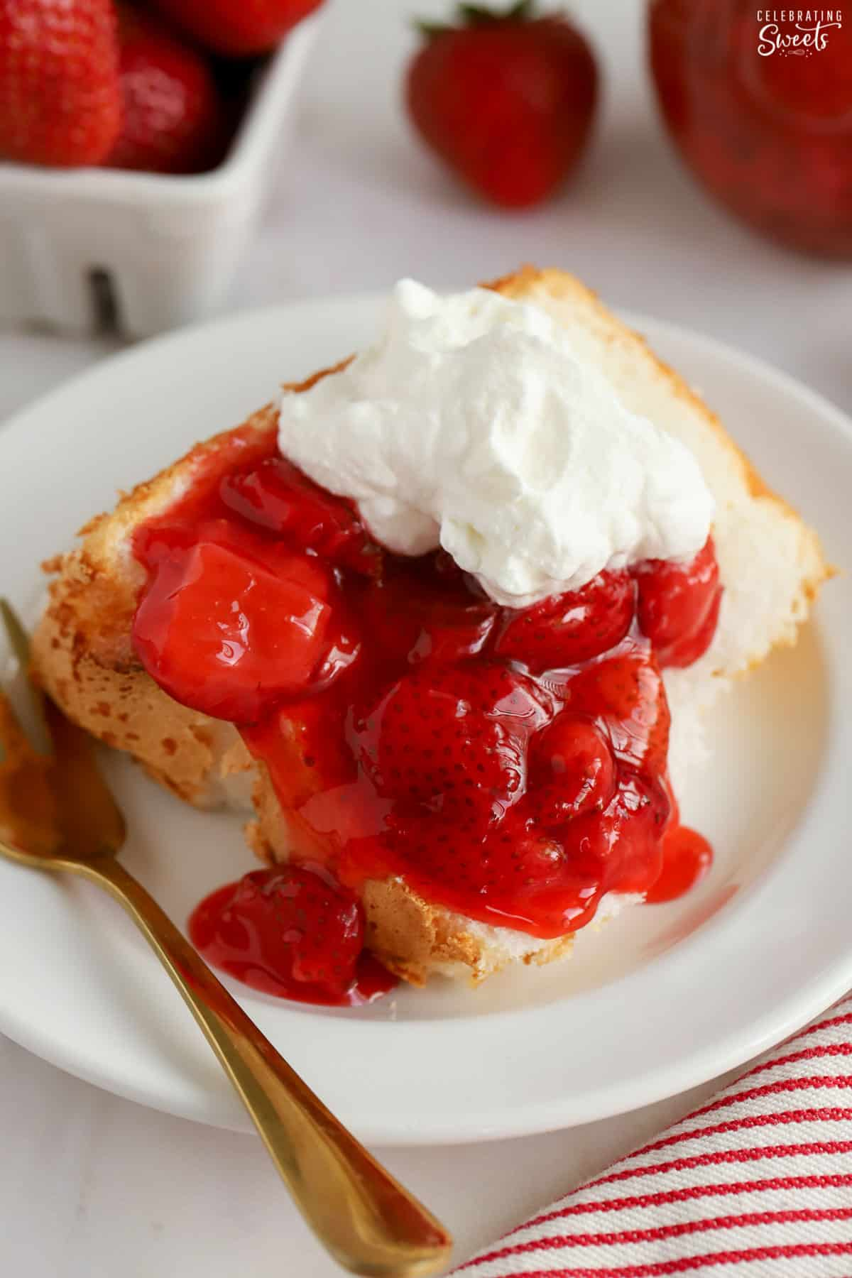 Strawberry sauce and whipped cream on a slice of angel food cake.