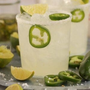 Spicy Margarita in a glass on a tray garnished with lime and jalapeno slices.