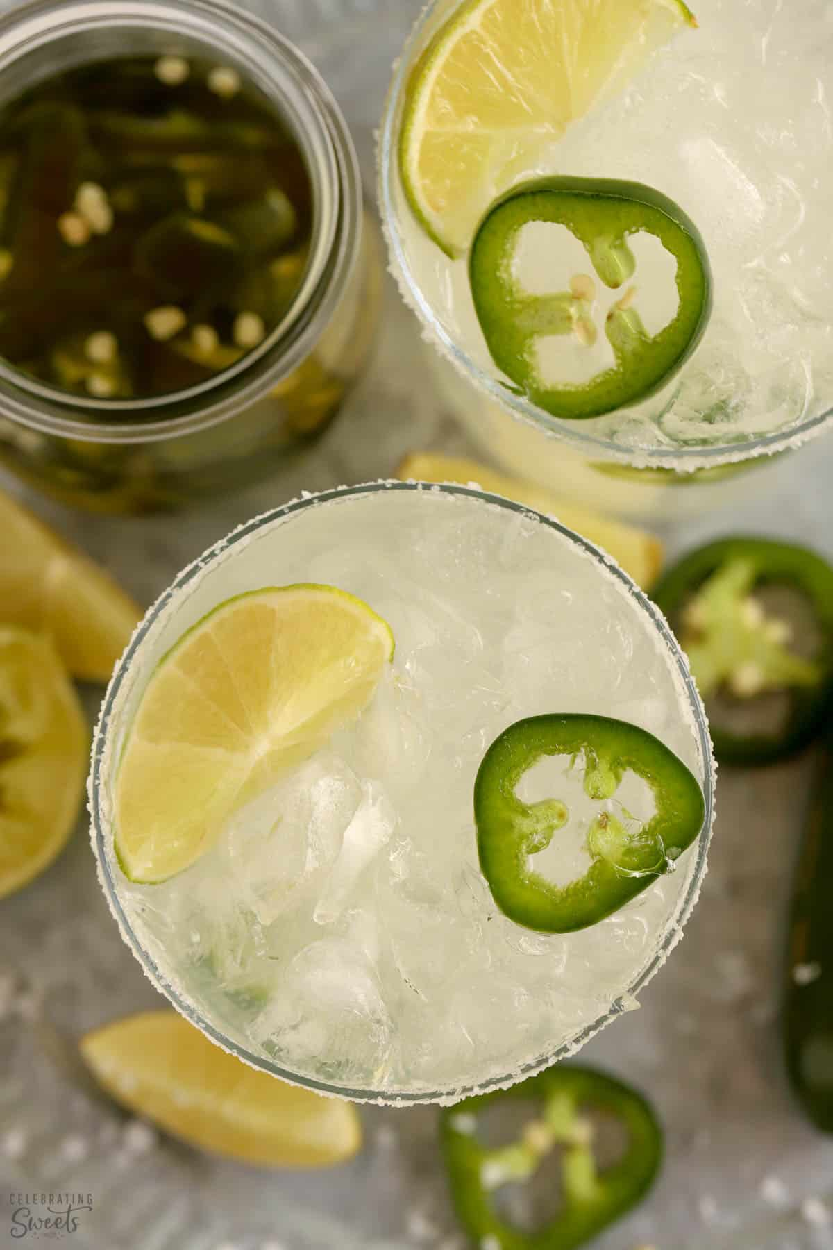 Overhead shot of two spicy margaritas garnished with lime and jalapeno.