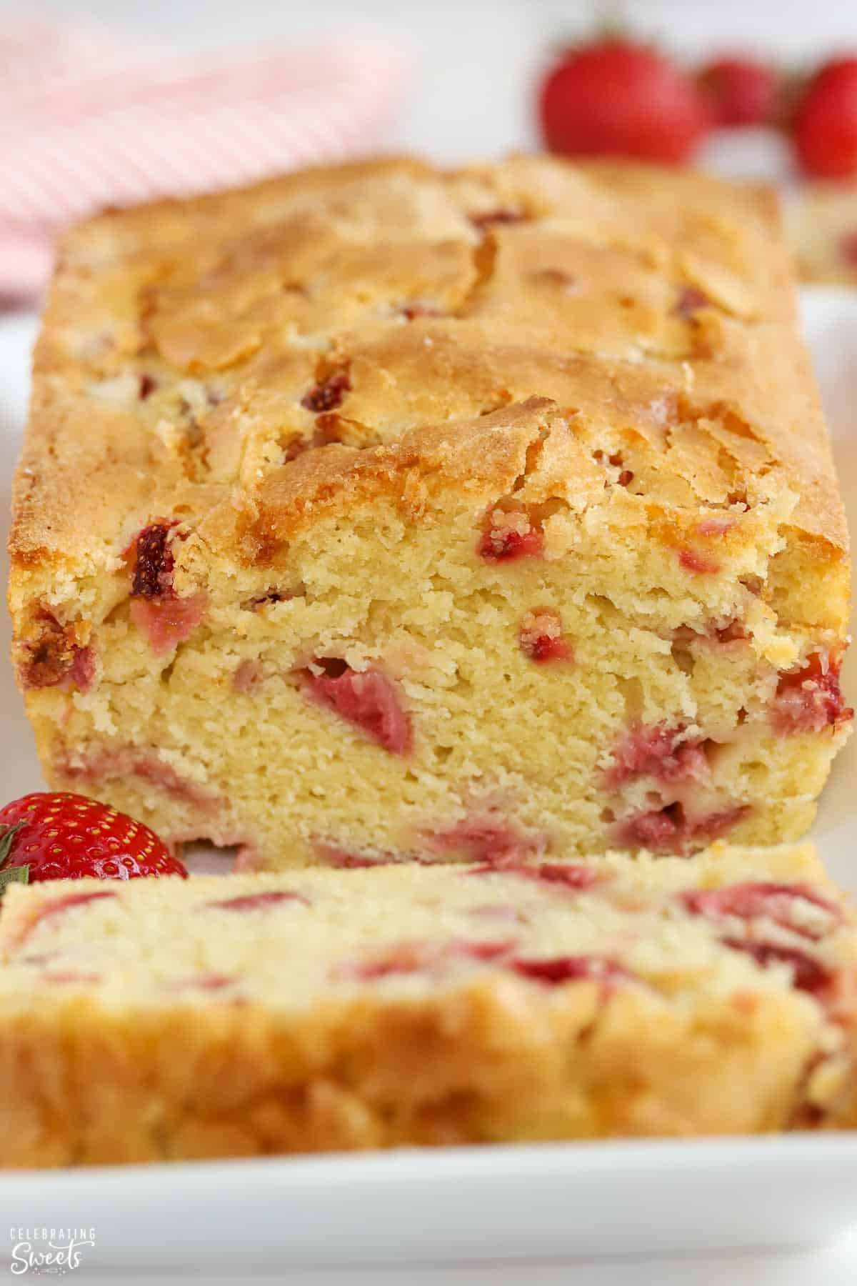 Loaf of strawberry bread on a white plate garnished with strawberries.