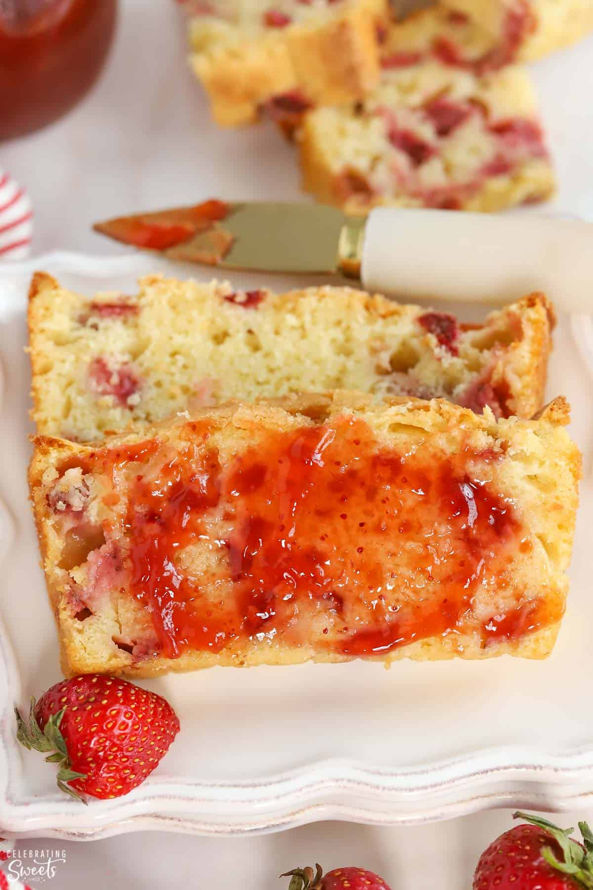 Two slices of strawberry bread on a white plate topped with strawberry jam.