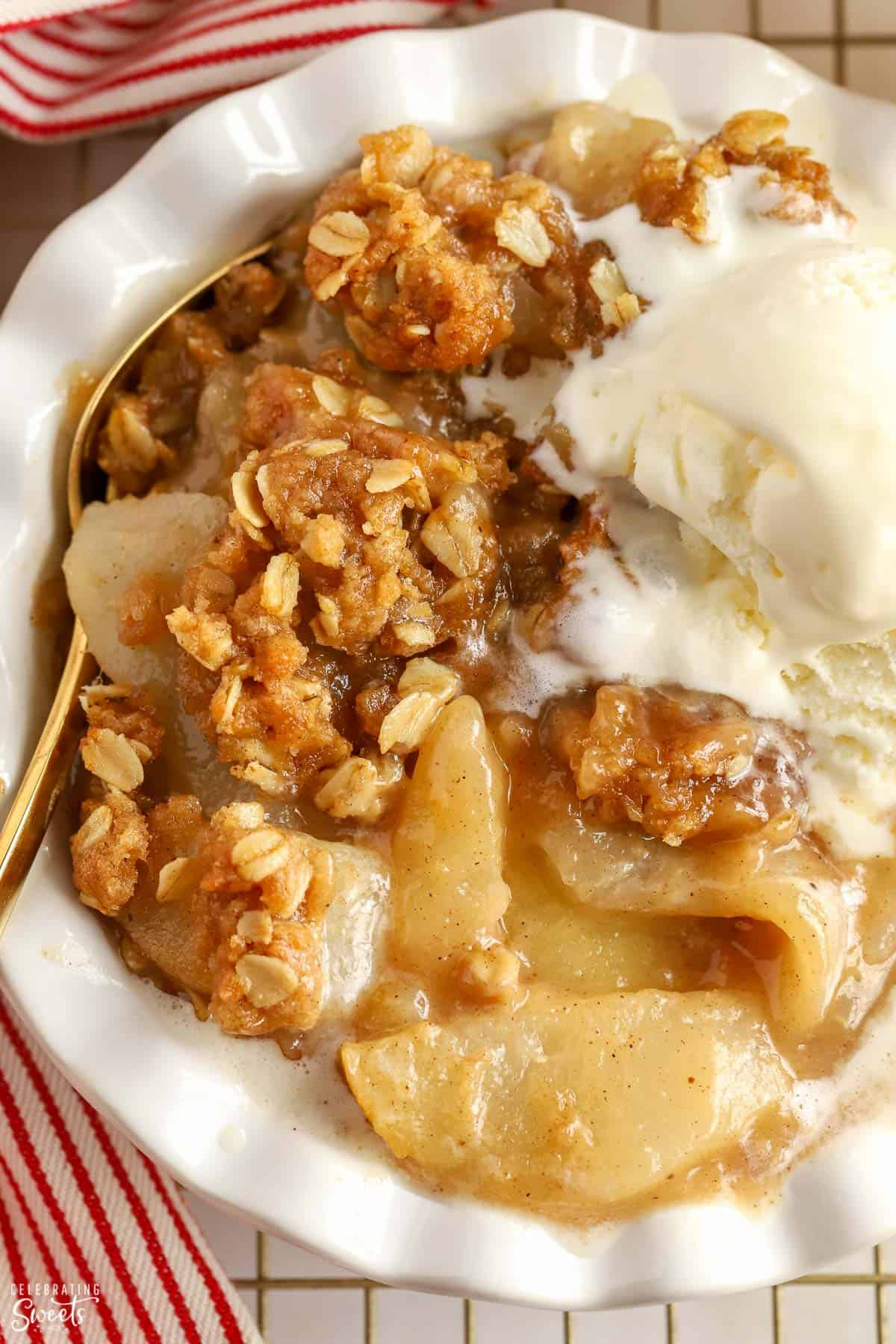 Closeup of Apple Pear Crisp topped with scoops of vanilla ice cream in a white bowl.