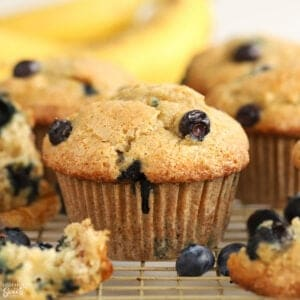 Closeup of blueberry banana muffins on a wire rack with bananas in the background.