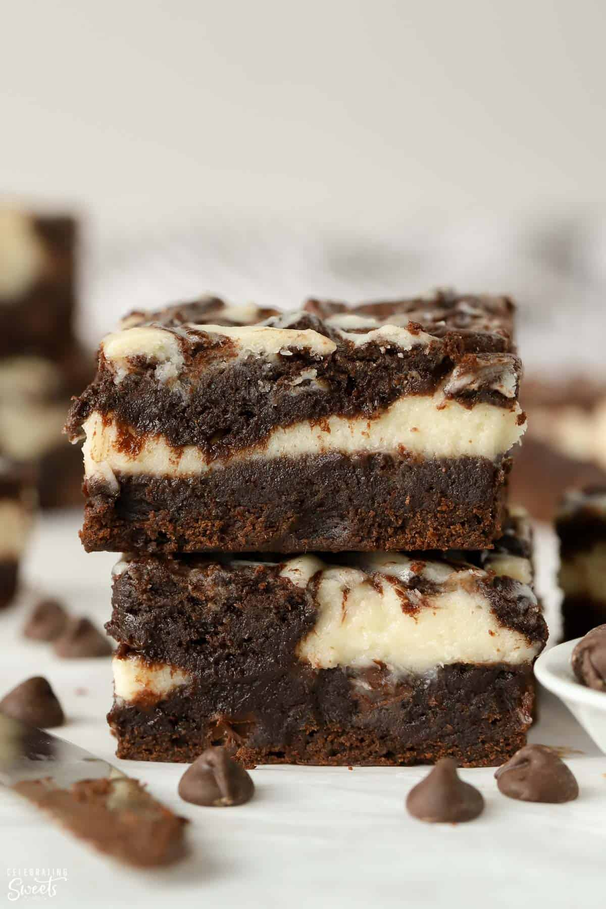 Stack of two cream cheese brownies on parchment paper.
