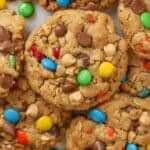 Closeup of Monster Cookies laying on parchment paper topped with M&M's and chocolate chips