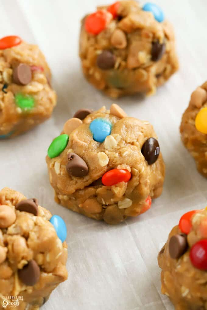 Cookie dough balls toped with M&M's and chocolate chips on a parchment lined baking sheet.