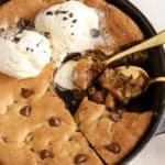 Chocolate chip skillet cookie in a cast iron skillet topped with ice cream