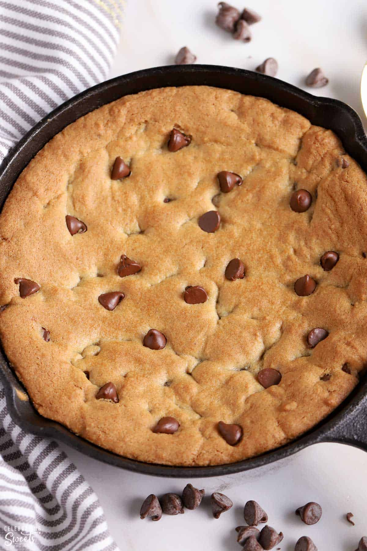 Overhead shot of a chocolate chip skillet cookie in a cast iron skillet.