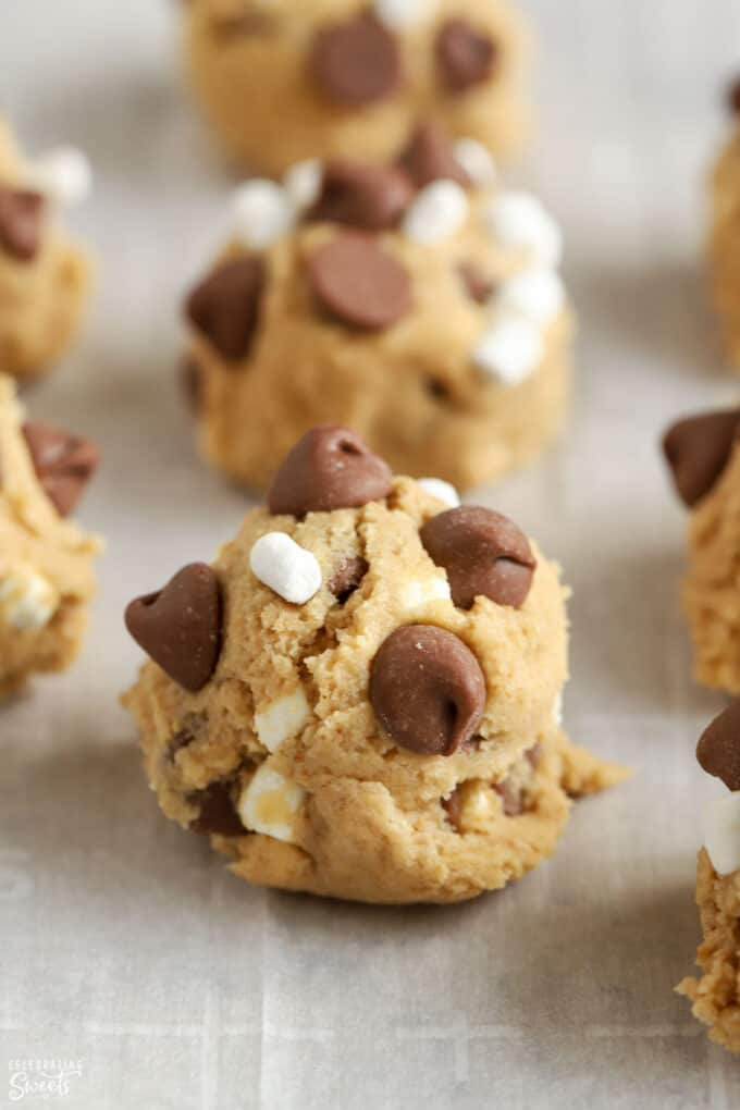 S'mores cookie dough balls on a parchment lined baking sheet.