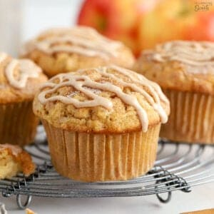 Apple cinnamon muffins on a wire rack topped with a cinnamon icing drizzle.