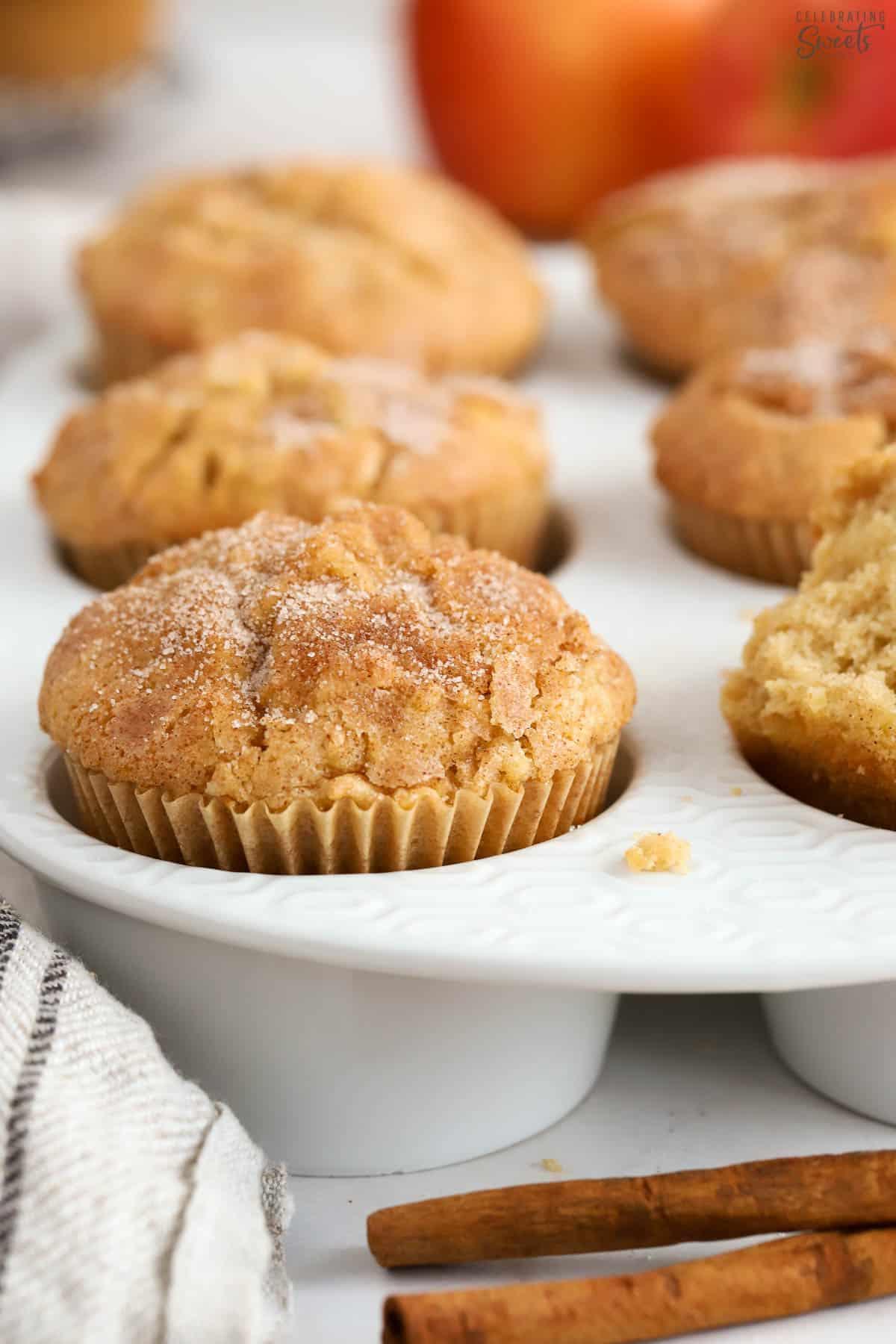 Apple cinnamon muffins in a white muffin baking dish.