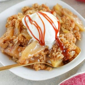 Apple crisp on a white plate topped with vanilla ice cream and caramel sauce.