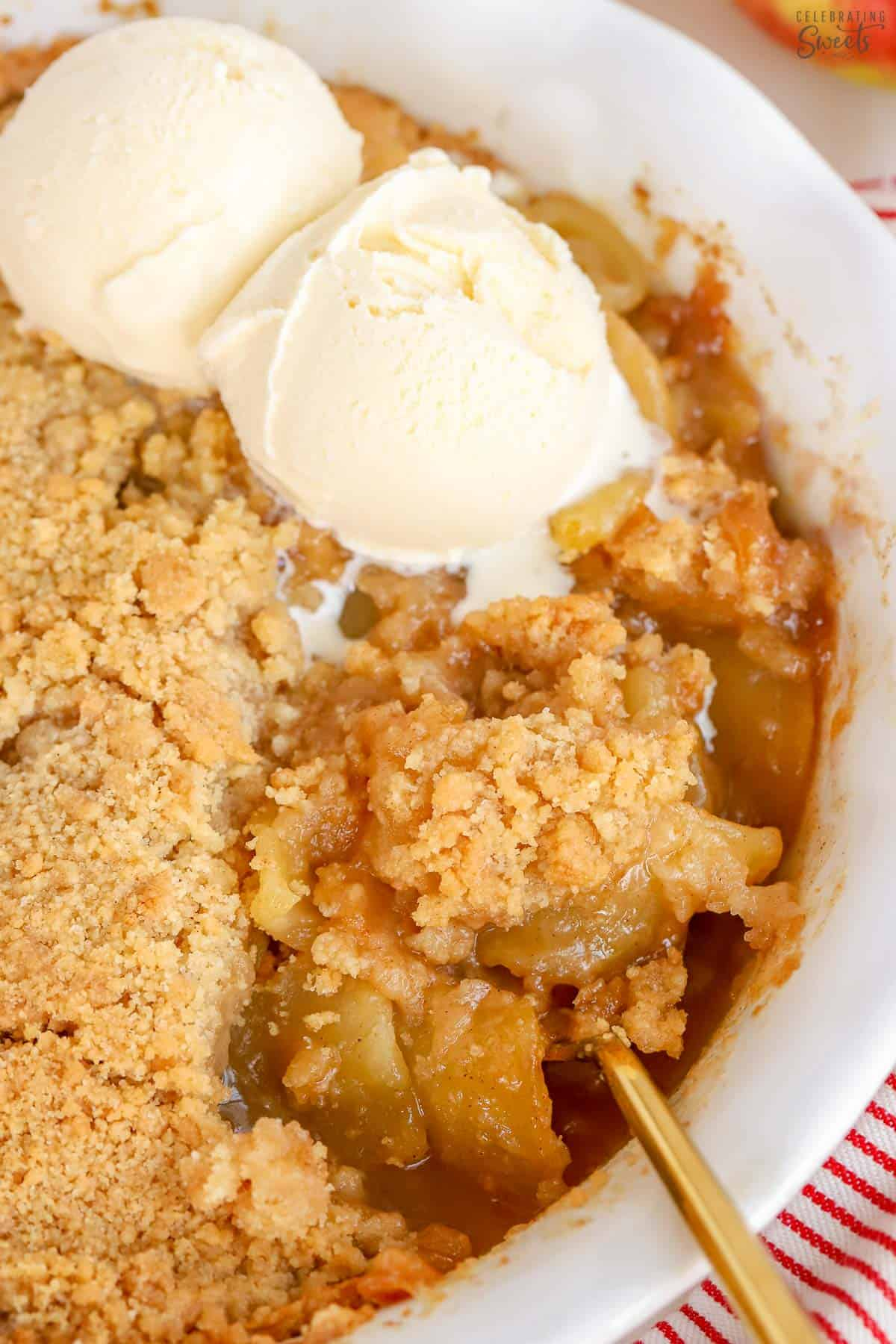 Apple crumble topped with two scoops of vanilla ice cream in a white baking dish.