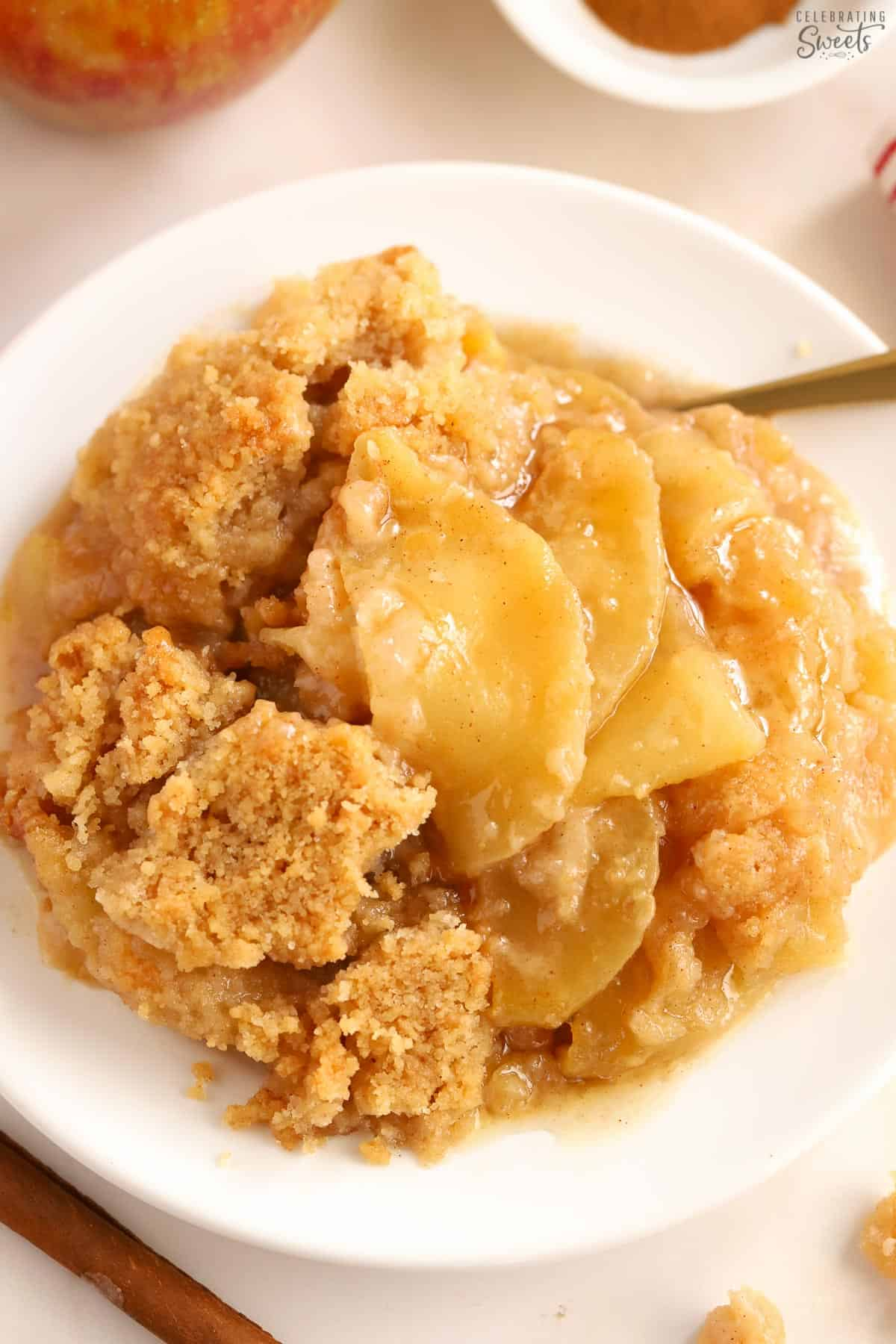 Apple crumble on a white plate with a gold fork.