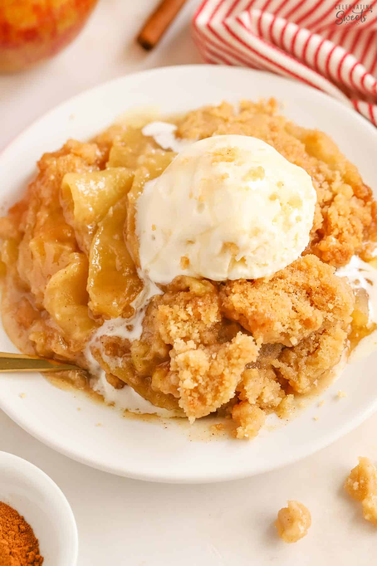Apple crumble on a white plate topped with a scoop of melty vanilla ice cream.