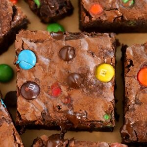 Closeup of M&M Brownies on brown parchment paper.