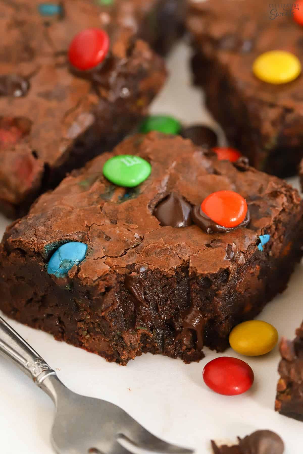 Closeup of an M&M Brownie next to a fork.