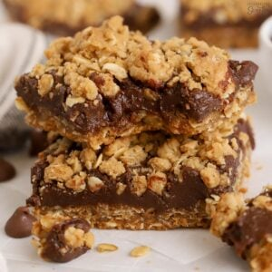Two Oatmeal Fudge Bars stacked on a piece of parchment paper.