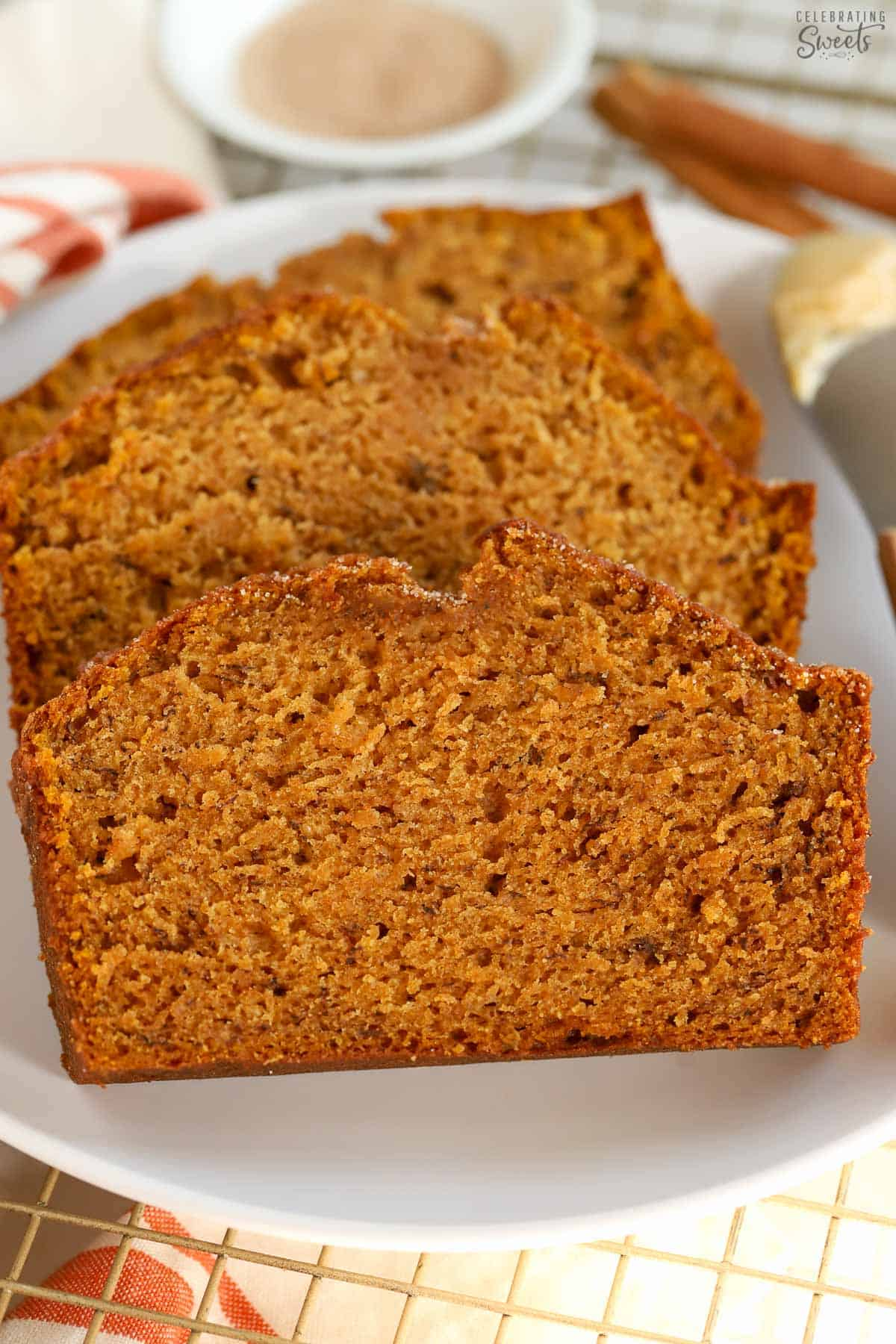 Three slices of pumpkin banana bread on a white plate.