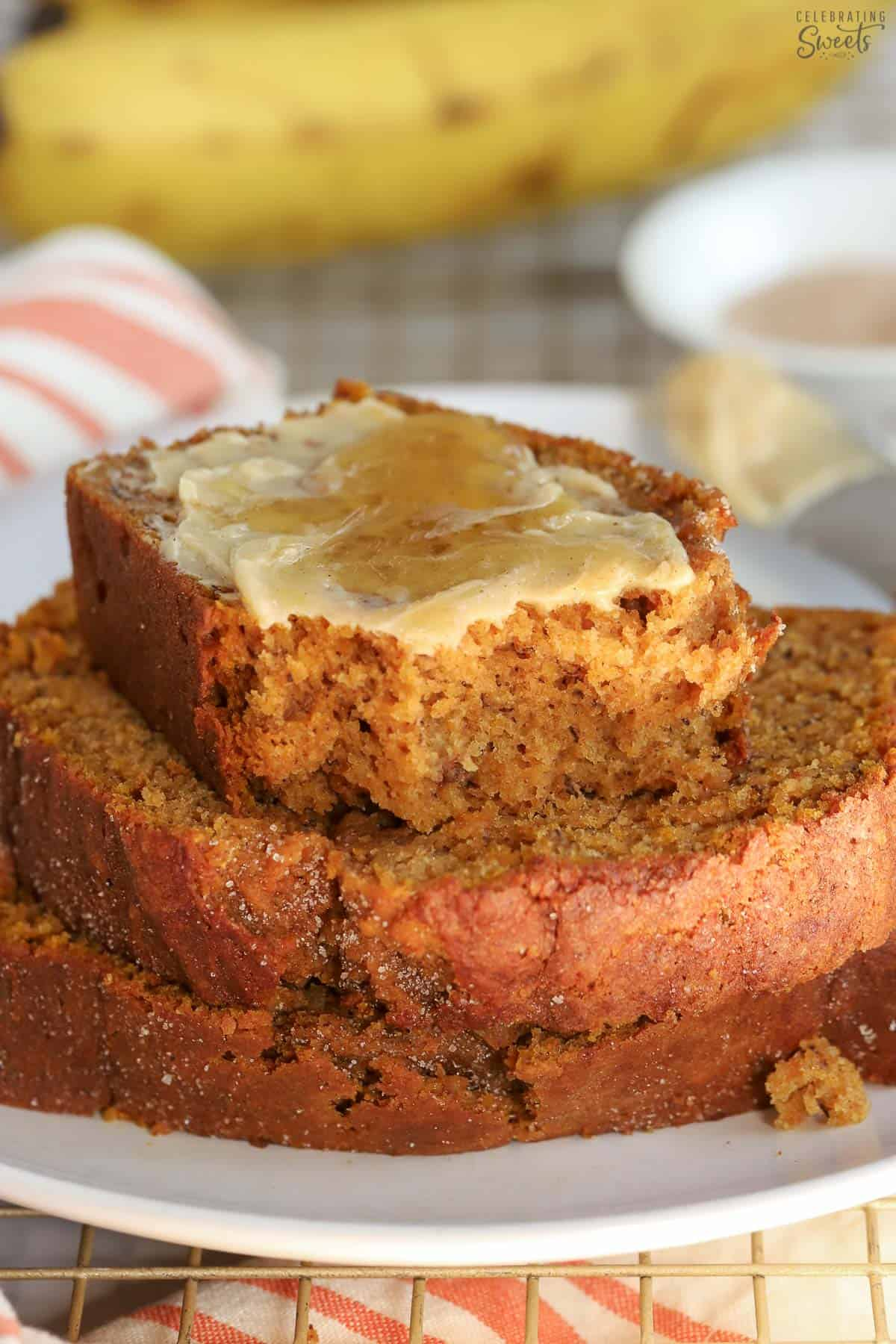 Three slices of pumpkin banana bread on a white plate with bananas in the background.
