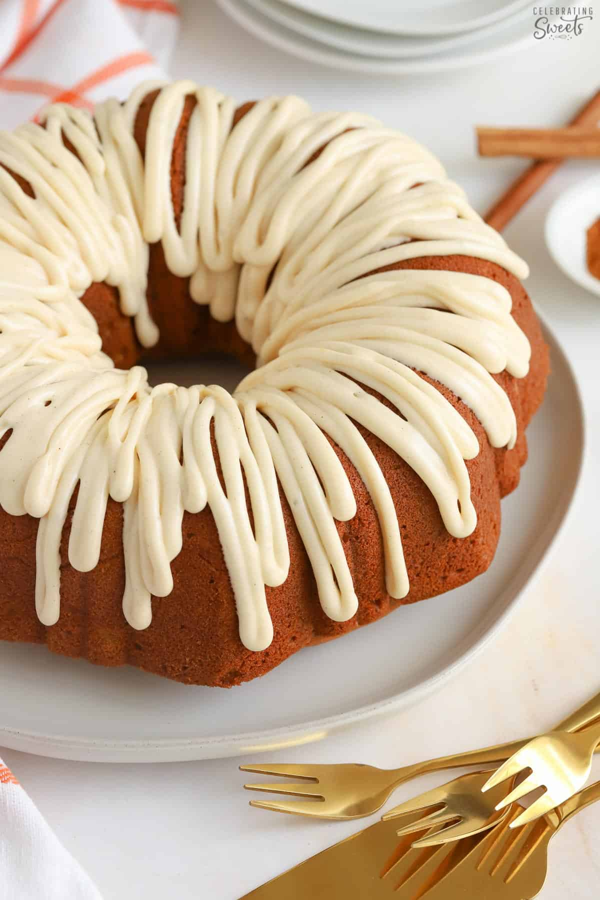 Pumpkin bundt cake drizzled with white icing sitting on a white plate next to gold forks.