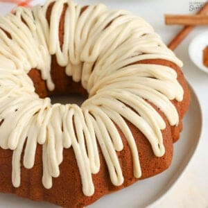 Pumpkin bundt cake drizzled with white icing sitting on a white plate.